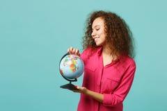 Portret van nieuwsgierig Afrikaans meisje in vrijetijdskleding die in de wereldbol houden die van de handenaarde op blauw turkooi royalty-vrije stock foto's