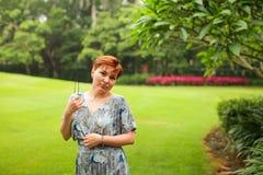 Portret van onbezorgde volwassen Kaukasische roodharigevrouw in kleding het stellen in groen de zomerpark royalty-vrije stock fotografie