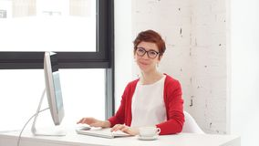 Portret van onderneemster die glazen dragen die aan computer werken en camera in bureau bekijken stock video