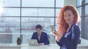 Portret van onderneemster die smartphone in modern bureau gebruiken stock footage