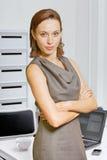 Portret van onderneemster met wapens op kantoor worden gekruist dat stock afbeelding