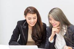 Portret van onderneemster twee die laptop in bureau met behulp van Wijfje binnen stock foto