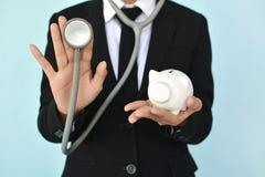 Portret van Onderneemsters met stethoscoop en wit spaarvarken Stock Foto