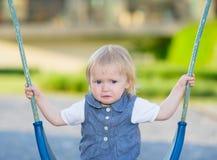Portret van ongelukkige babyzitting op schommeling Royalty-vrije Stock Afbeeldingen