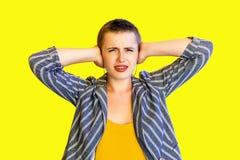 Portret van ongelukkige jonge korte haar mooie vrouw in geel overhemd en gestreept kostuum die en gesloten haar oren met hand bev stock afbeelding
