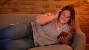 Portret van ontspannen plus grootte langharig model die op bank die vreugdevol op smartphone babbelen in comfortabele huisatmosfe stock videobeelden