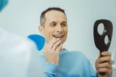 Portret van opgetogen patiënt dat het controleren zijn tanden royalty-vrije stock foto's
