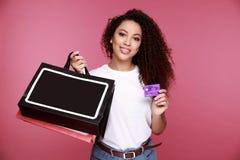Portret van opgewekte jonge Afrikaanse die vrouwenholding het winkelen zakken en het tonen van creditcard over beige achtergrond  stock foto's