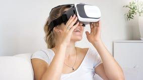 Portret van opgewekte jonge vrouw die 360 graad op video in VR-hoofdtelefoon letten Royalty-vrije Stock Foto's