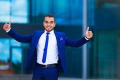 Portret van opgewekte jonge zakenman in blauw kostuum die zich op c bevinden stock afbeelding