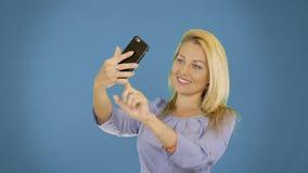 Portret van opgewekte vrolijke glimlachende jonge mooie vrouw die selfie foto op smartphone maken Stevige achtergrond stock videobeelden