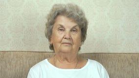 Portret van oude grootmoeder met strikte blik stock video