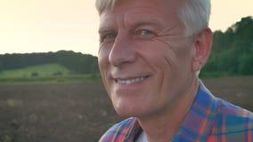 Portret van oude landbouwer die camera en glimlachend, gecultiveerd gebied tijdens ochtend op achtergrond bekijken, gelukkig en b stock videobeelden