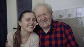 Portret van oude vader en jonge dochter die bij camera glimlachen 4K stock footage