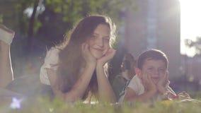 Portret van oudere zuster en jongere broer in openlucht De jongen en het meisje die op het gras samen in park het kijken liggen stock footage