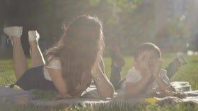 Portret van oudere zuster en jongere broer in openlucht De jongen en het meisje die op het gras samen in het park liggen De zomer stock footage