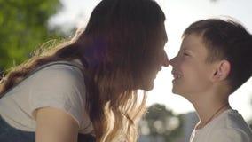 Portret van oudere zuster het besteden tijd met jongere broer in openlucht De jongen en het meisje die neuzen in het park wrijven stock video