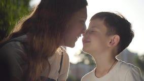 Portret van oudere zuster het besteden tijd met jongere broer in openlucht De jongen en het meisje die neuzen in het park wrijven stock videobeelden