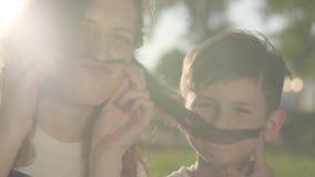 Portret van oudere zuster het besteden tijd met jongere broer in openlucht De jongen en het meisje die valse snorren met haar mak stock footage