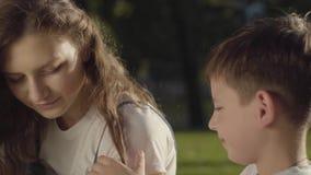 Portret van oudere zuster het besteden tijd met jongere broer in openlucht De jongen wat betreft haar van het meisje in het park stock footage