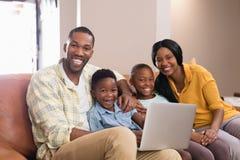 Portret van ouders en kinderen die laptop houden terwijl het zitten op bank stock foto's