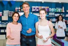 Portret van ouders met dochtertiener het winkelen in drugstor Stock Foto's