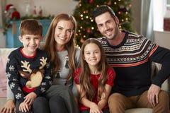 Portret van Ouders met Kinderen die Feestelijke Verbindingsdraden dragen die op Sofa In Lounge At Home op Kerstmisdag zitten royalty-vrije stock foto