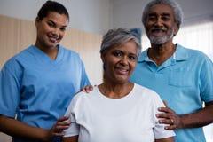 Portret van oudsten met verpleegster in pensioneringshuis stock afbeeldingen