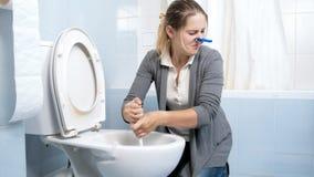 Portret van overgevoelig jong vrouwen schoonmakend toilet met borstel royalty-vrije stock foto