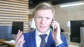 Portret van overwerkte droevige zakenmanholding telefoon en het schreeuwen stock footage