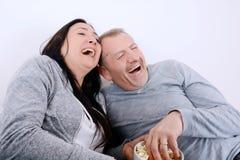 Portret van paar het lachen het letten op televisie en het eten van pop c stock afbeeldingen