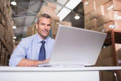 Portret van pakhuismanager met laptop stock foto