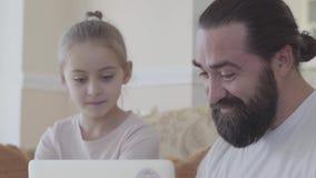 Portret van papa met leuke dochter en laptop zitting in de woonkamer op de laag en het spreken over grappig iets stock videobeelden