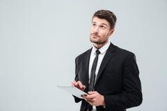 Portret van peinzende jonge zakenman die en tablet denken gebruiken royalty-vrije stock fotografie