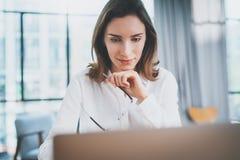 Portret van peinzende zekere onderneemster die met laptop computer op modern kantoor werkt Vage achtergrond royalty-vrije stock foto