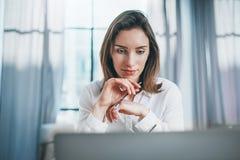 Portret van peinzende zekere onderneemster die met laptop computer op modern kantoor werkt Vage achtergrond royalty-vrije stock afbeeldingen