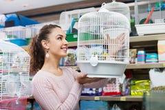 Portret van positief mooi meisje die vogelkooi kiezen stock afbeeldingen