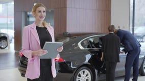 Portret van prettige vrouw in roze jasje met een groot boek over auto's voor paar die voertuig kiezen De mens opent stock videobeelden
