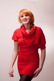 Portret van redhead schoonheid in rode kleding, het glimlachen Royalty-vrije Stock Fotografie