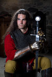 Portret van Ridder With Sword Sitting tegen Stonewall en weg het Kijken Stock Afbeelding