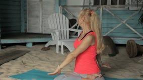 Portret van rijpe dame, die yoga buiten opleiding, dichtbij blauw huis heeft stock videobeelden