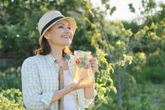 Portret van rijpe gelukkige vrouw in hoed in de tuin met natuurlijke eigengemaakte kruidendrank met muntaardbeien royalty-vrije stock afbeeldingen