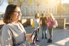 Portret van rijpe glimlachende vrouwelijke leraar in glazen met klembord, outdor met een groep tienersstudenten stock foto's