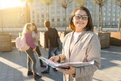 Portret van rijpe glimlachende vrouwelijke leraar in glazen met klembord, outdor met een groep tienersstudenten stock afbeeldingen