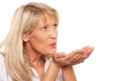 Portret van rijpe vrouw die een geïsoleerde kus blazen Royalty-vrije Stock Foto