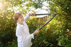 Portret van rijpe vrouwelijke tuinman Vrouw die met secateur in binnenlandse tuin bij de zomerdag werken royalty-vrije stock fotografie