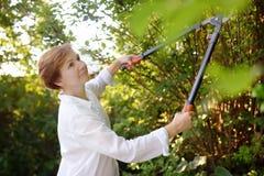 Portret van rijpe vrouwelijke tuinman Vrouw die met secateur in binnenlandse tuin bij de zomerdag werken royalty-vrije stock foto's
