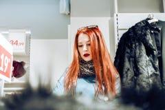 Portret van rood haar jong meisje in een blauw leerjasje de vrouw in de opslag kiest een bontjas royalty-vrije stock foto's