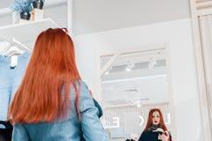 Portret van rood haar jong meisje in een blauw leerjasje die op kleren dichtbij de spiegel proberen royalty-vrije stock fotografie