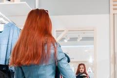 Portret van rood haar jong meisje in een blauw leerjasje die op kleren dichtbij de spiegel proberen stock foto's